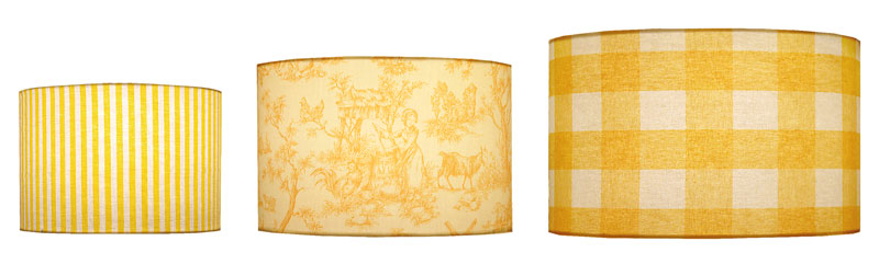 Different sizes of cylinder shape lampshades in stripe, toile and check fabric print designs in a variety of yellow colors.