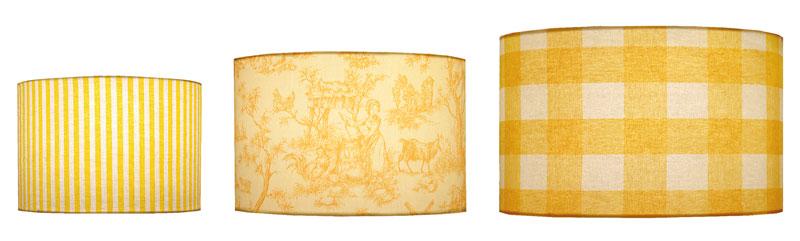 Différentes tailles d'abat-jour cylindriques en tissus imprimés à rayures, toiles de Jouy et carreaux aux couleurs de jaunes variés.
