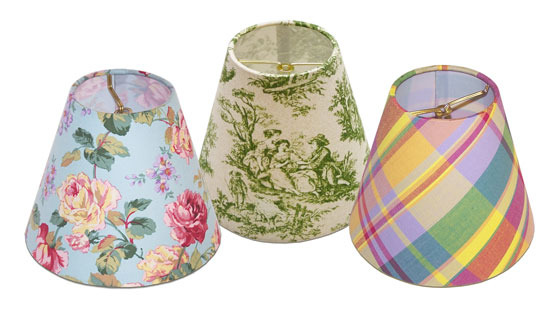 Small lampshades with flame clip fitters in various flower, toile and check printed fabrics for chandeliers or sconces.